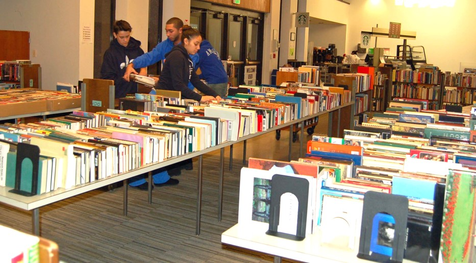EOP students arrange used books on long tables for the Friends of the Library Used Book Sale