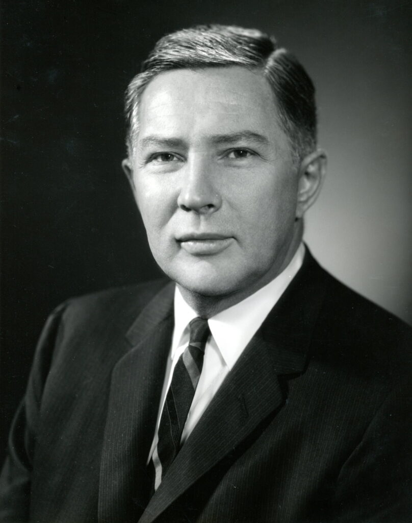 Portrait of Dean William J Haggerty in a dark suit and tie.